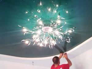 Натяжной потолок и освещение как выбрать свет? 111nk604axhНатяжной потолок является одним из самых актуальных и модных способов отделки. Под натянутым полотном он скрывает бугры, вмятины и прочие изъяны поверхности. Бытует ошибочное мнение, что на натяжной потолок можно монтировать только точечные источники света, а от классических люстр и прочих источников освещения придется отказаться. Это не так. Для комнаты с натяжными потолками подойдет практически любая люстра, а также ЛЕД-светильники, точечные источники света и их комбинации.Нужно лишь придерживаться некоторых правил, которые касаются конструкции, мощности и материалов, из которых изготовлены светильники, и знать кое-какие секреты монтажа. В статье пойдет речь о том, как правильно подобрать и установить светильники на натяжной потолок.  О натяжных потолках.  Этот новый вид отделки представляет собой синтетическое полиэфирное полотно (или ПВХ), которое натягивается на несколько сантиметров ниже настоящего потолка. Это достаточно деликатный материал: полотно ПВХ может растягиваться при нагревании до 80 град. и выше, а полиэфирные волокна имеют свойство темнеть или желтеть, находясь рядом с горячим источником света. Выбирая лампу, которую вы будете устанавливать на такой потолок, помните о следующем:  - полотно потолка нежелательно нагревать больше, чем на 60 градусов. Конструкция люстры и мощность источников света должна быть такой, чтобы это условие соблюдалось;  - в пространстве между потолком и натяжным потолком нельзя располагать преобразователи, которые требуются для определенных типов ламп (светодиодных, галогеновых). Это опасно, и такие устройства за потолком очень часто ломаются. Но за поверхностью натяжного потолка можно прятать проводку.  - лампы и люстры нужно приобрести заранее. Они крепятся к основному потолку перед началом монтажа.  Натяжной потолок имеет глянцевую поверхность, прекрасно отражающую свет (до 80%). Поэтому, лучше не направлять поток света непосредственно на потолок. Возможно он буде